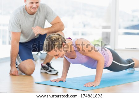 Male trainer assisting woman with push ups in fitness studio