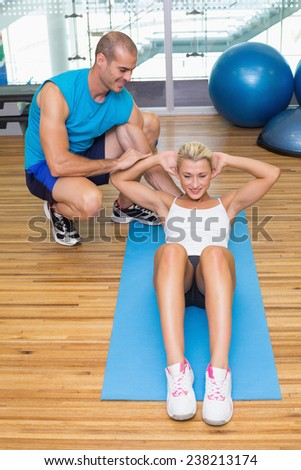 Male trainer assisting young woman with abdominal crunches at fitness studio - stock photo