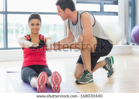 Male trainer assisting young woman with pilate exercises in the fitness studio - stock photo