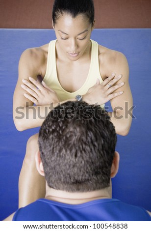 Male trainer helping woman do sit ups
