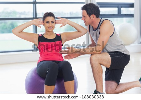 Male trainer helping young woman do abdominal crunches on fitness ball at a bright gym - stock photo