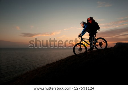 male traveler heading off the evening with a mountain bike - stock photo