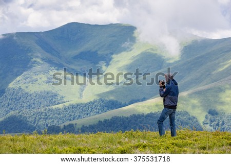 Male traveler photographing beautiful mountains - stock photo