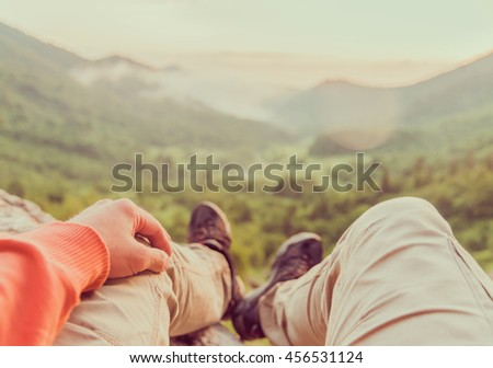 Male traveler sitting in summer mountains at sunset, point of view shot. Toned image - stock photo