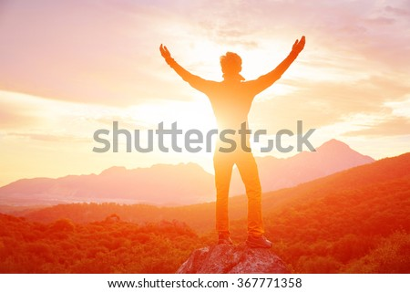 male traveler  standing on the cliff against mountains and cloudy  sky at early morning. man stands hands up - stock photo