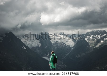 male traveller on the top of mountain stormy landscape - stock photo