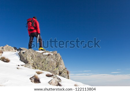 Male trekker standing on a rock while observing the horizon. Clear blue sky in background. - stock photo