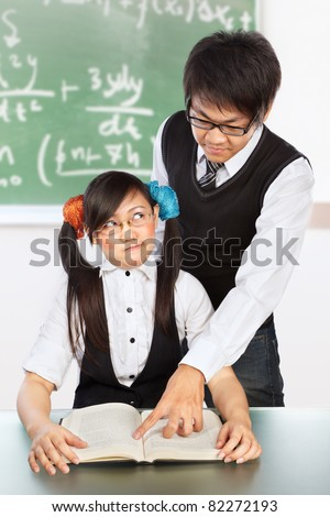 Male tutor teaching the nerd female student in classroom - stock photo