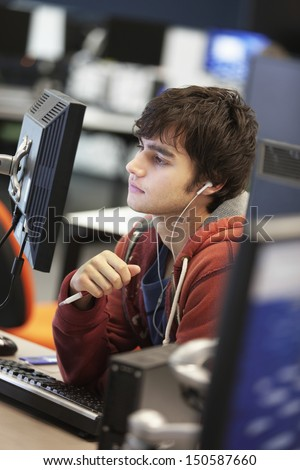 Male university student using computer while listening to music in college - stock photo
