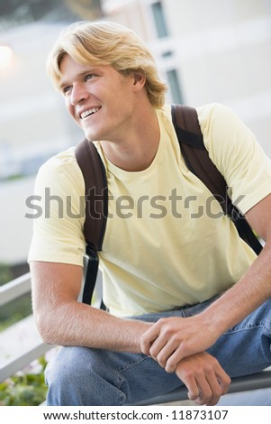 Male university student wearing rucksack outside - stock photo