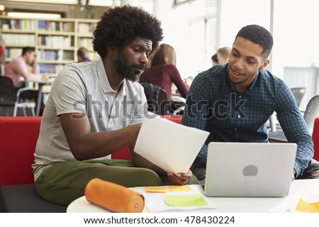 Male University Student Working In Library With Tutor