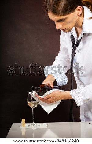 Male waiter or butler serving pouring white wine into glass.