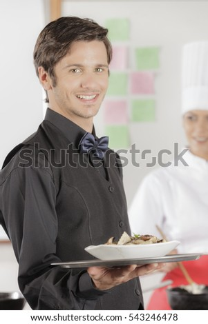 Male waiter receiving his next order from an attractive female cook in industrial kitchen wearing black uniform