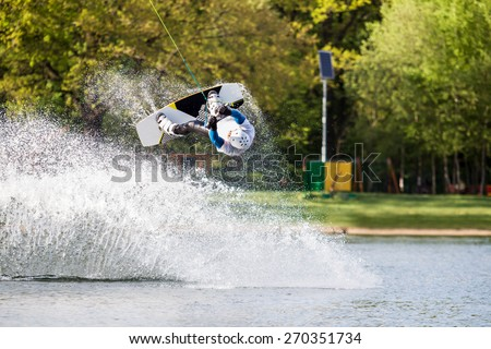 Male wakeboarder jumps over spray on pond in park - stock photo