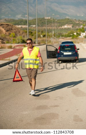Male walking with a triangle to secure his broken down car - stock photo