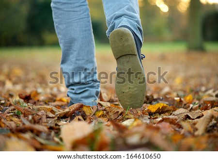 Male walking with boots on autumn leaves - stock photo