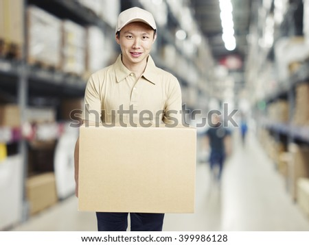 male warehouse worker carrying a carton box of goods in a cash and carry wholesale store. - stock photo