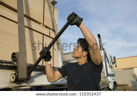 Male warehouse worker loading wood on a trailer
