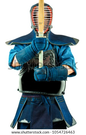 Male wearing a kendo armor with helmet and gloves holding a bamboo sword, standing position.