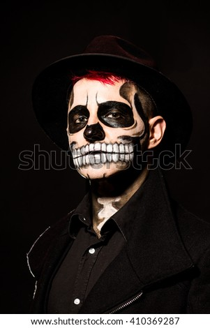 Male wearing hat with scary authentic skull face make up. Black background, studio shot. Dressed in black coat.