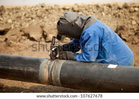 Male welder worker wearing protective clothing fixing welding and grinding industrial construction oil and gas or water plumbing pipeline outside on site