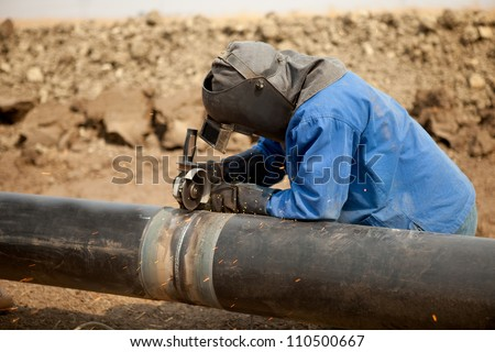 Male welder worker wearing protective clothing fixing welding and grinding industrial construction oil and gas or water and sewerage plumbing pipeline outside on site