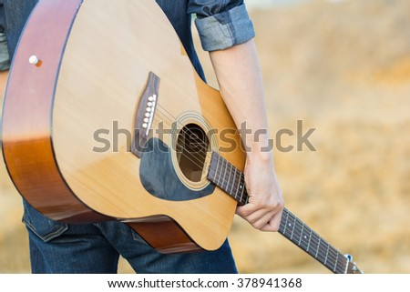 Male with acoustic guitar outdoor - stock photo