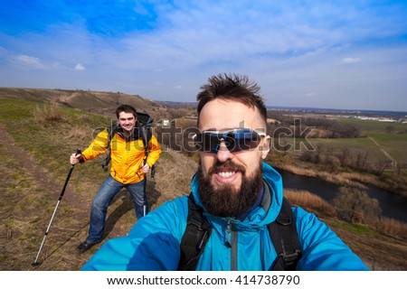male with friend hiker taking photo with smart phone in forest, looking at camera, copy space for text or slogan - stock photo
