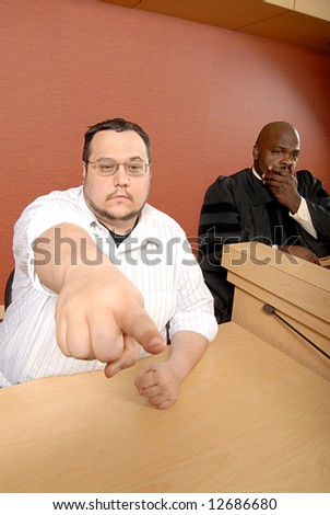 Male witness pointing out someone in the crowd while the judge watches on - stock photo