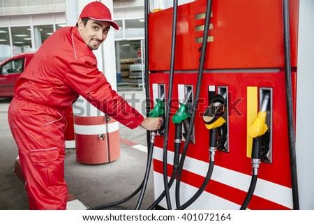 Male Worker At Gas Station Filling Up Customers Car With Petrol - stock photo