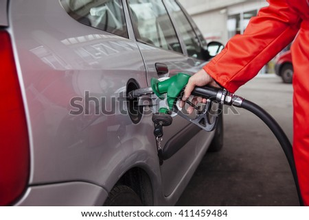 Male Worker At Gas Station Filling Up Customers Car With Petrol