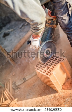 Male worker cutting bricks with angle grinder power tool, dust and debris on construction site - stock photo