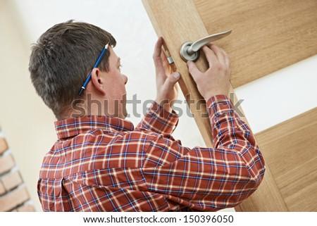 Male worker handyman carpenter at lock installation into wood door - stock photo