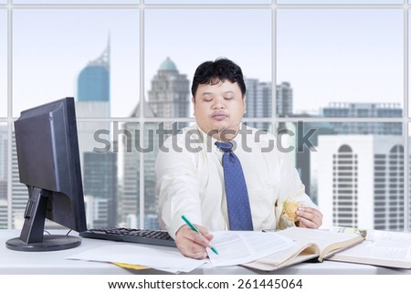 Male worker holding a burger while writing on a paper in the office, shot at workplace - stock photo