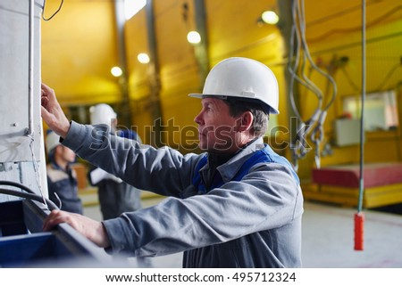 Male worker in overalls and helmet presses a button on the control panel equipment at the plant