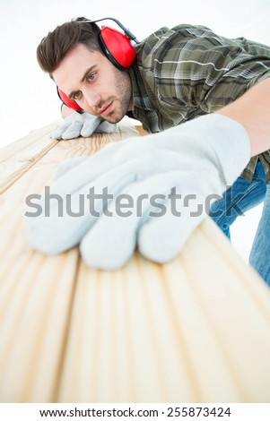 Male worker measuring wooden plank on white background