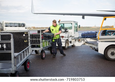 Male Worker Placing Luggage In Trailer On Runway