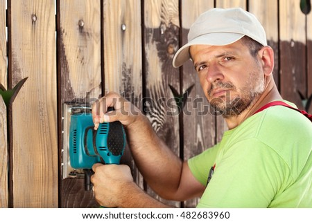 Male worker polishing old wooden fence with power tool - a vibrating sander
