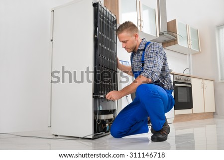 Male Worker Repairing Refrigerator With Screwdriver In House - stock photo