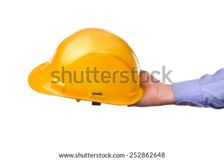 Male worker's hand holding yellow industrial protective helmet. Part of series set of images with DIY tools for home jobs and crafts in hand isolated on white background. - stock photo