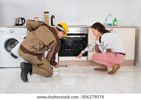 Male Worker Spraying Insecticide In Front Of Housewife In Kitchen - stock photo