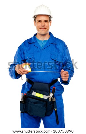 Male worker stretching measuring tape isolated against white background - stock photo