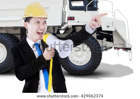 Male worker using a megaphone for screaming with a big truck on the background, isolated on white background - stock photo