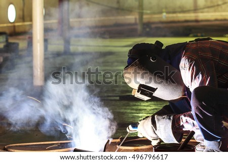 Male  worker wearing protective clothing and repair welding industrial construction oil and gas or  storage tank inside confined spaces.