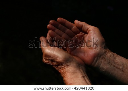 male Wrinkled old hands begging asking for money, help, reaching out and compassion concept - stock photo
