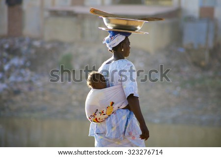 MALI, MOPTI, DECEMBER 28: Unidentified Woman carrying a baby in her back in the streets of Mopti. 2010 - stock photo