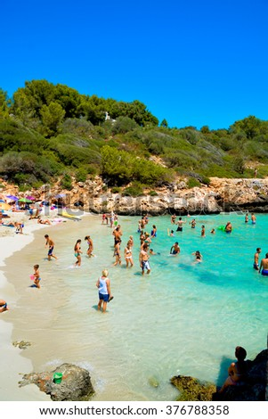MALLORCA, SPAIN - AUGUST 1, 2015:  sandy beach with people sunbathing and playing on a sunny summer day on August 1, 2015 in Mallorca, Balearic islands, Spain.  - stock photo