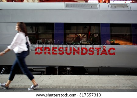MALMO, SWEDEN - FRIDAY, AUGUST 21, 2015: A pedestrian walks past a train at the main station in Malmo, Sweden.  - stock photo