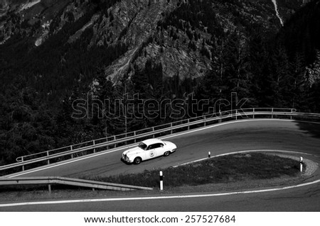 MALOJA PASS, SWITZERLAND - JUNE 14: A white Jaguar S-Type takes part to the Summer Marathon classic car race on June 14, 2014 near Maloja Pass. This car was built in 1965  - stock photo