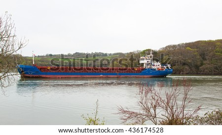 MALPAS, ENGLAND - MAY  6, 2016: A general cargo ship en route to the river Fal and the sea beyond. Access to and from the nearby ancient port of Truro is severely depth restricted